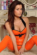 Rae poses in her orange latex up in the bedroom