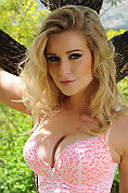 Jess Davies poses in her pretty lingerie under a tree