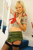 Sexy blonde in uniform and stockings shows off on the stairs