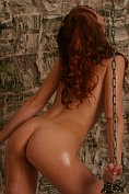 Oiled-up babe plays with chains in the dungeon