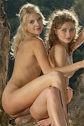 Two gorgeous slim girls pose naked together out in the countryside