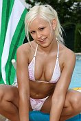 Peroxide blonde teen takes off her bikini and gets oiled up