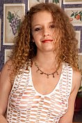 Curly-haired Gwenevieve undresses and inserts a cucumber