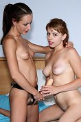 Lexi Belle and another girl play with a strap-on
