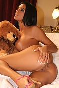 Busty babe Ashley Bulgari poses naked on the bed with her teddy