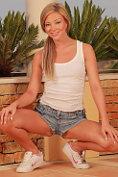 Smiling blonde Natalia Forrest stripteasing