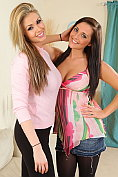 Two beauties help each other to remove their casual outfits.