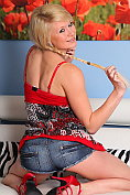 Cute Tegan in sexy denim hotpants strips naked to play on the sofa
