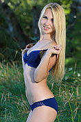 Beautiful blonde teen Belonika takes off her matching bra and knickers set in the garden