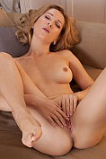 Genevieve Gandi strips naked and masturbates on the sofa with her legs open