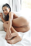 Apolonia lays naked on the bed