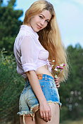 Busty blonde babe Genevieve Gandi takes off her shirt and her denim shorts out in the country
